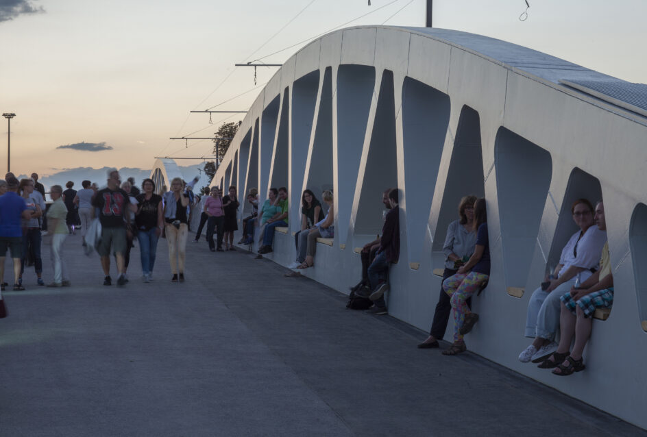 People and walking and sitting on Kienlesberg bridge with sunset backdrop