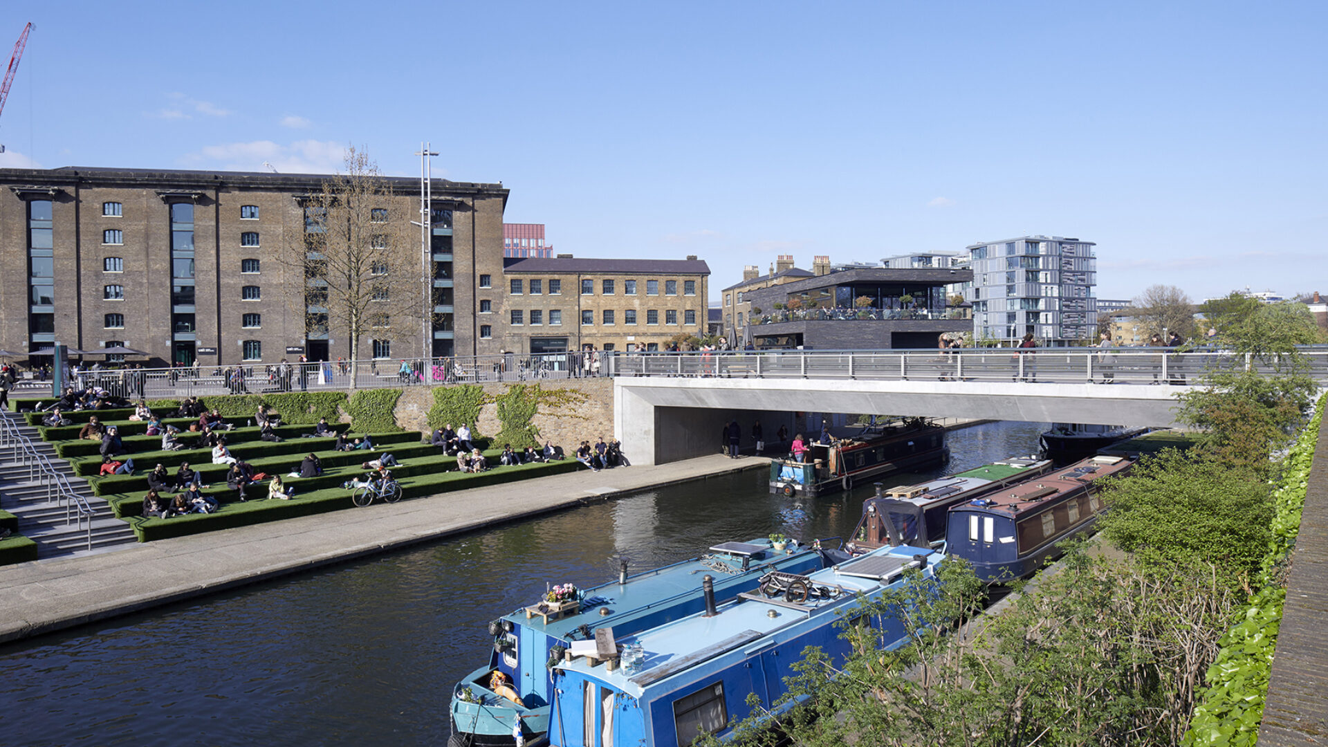 Grass steps and canal boats at Regents Canal bridge, Kings Cross
