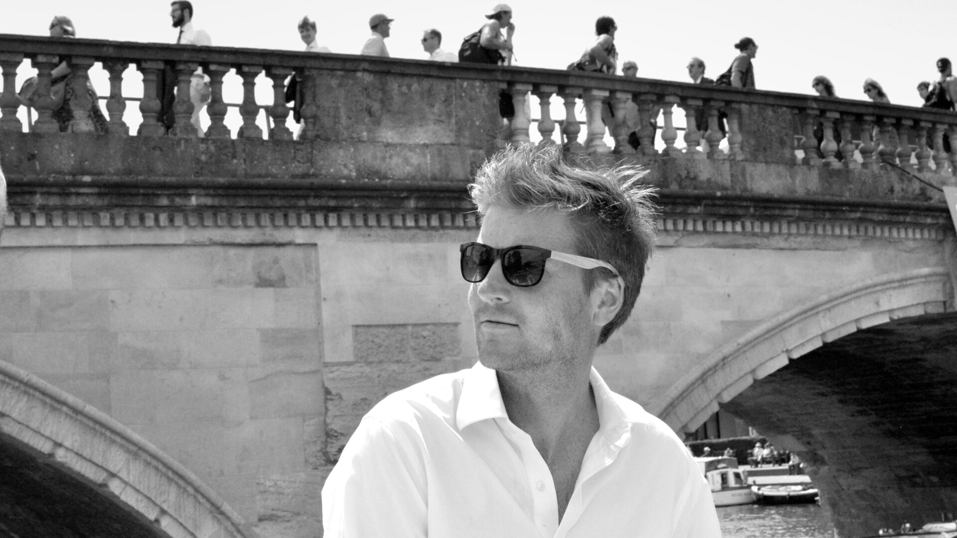 Black and white photo of Sam White wearing sunglasses in front of a classical stone bridge
