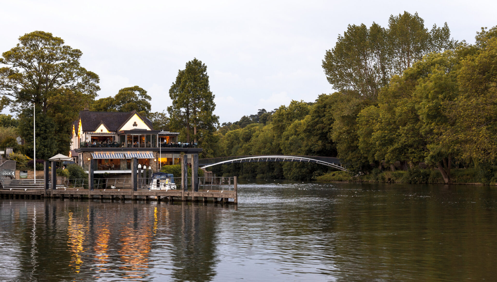 Early evening view down river looking West at the footbridge with Boulters Restaurant to the left