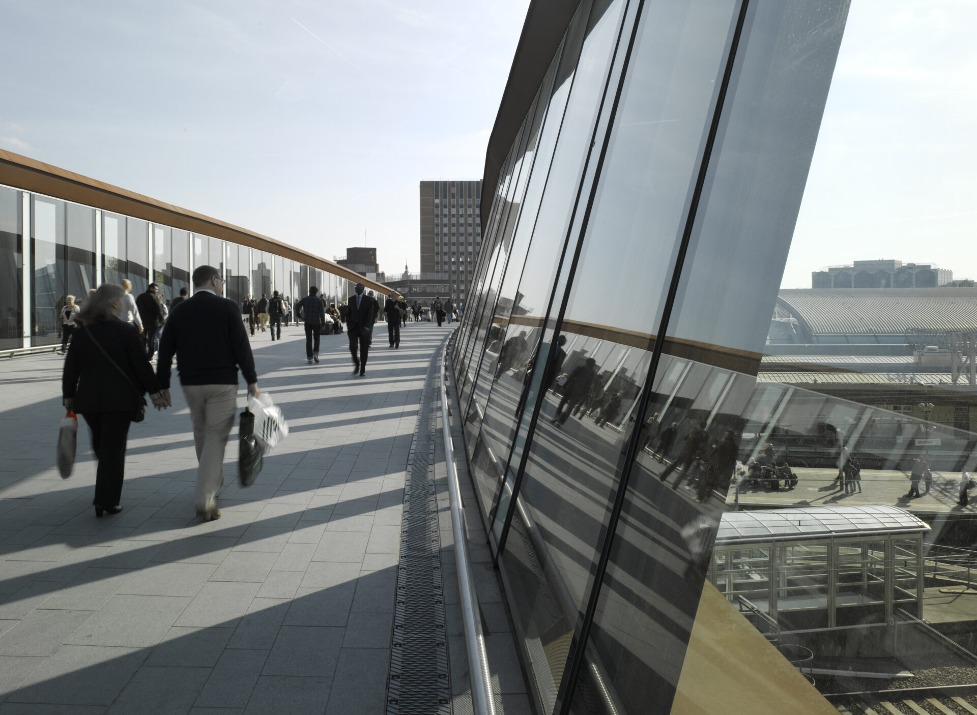 Reflection in the glass of the parapet of people walking across Town Centre Link Bridge at Westfield, Stratford