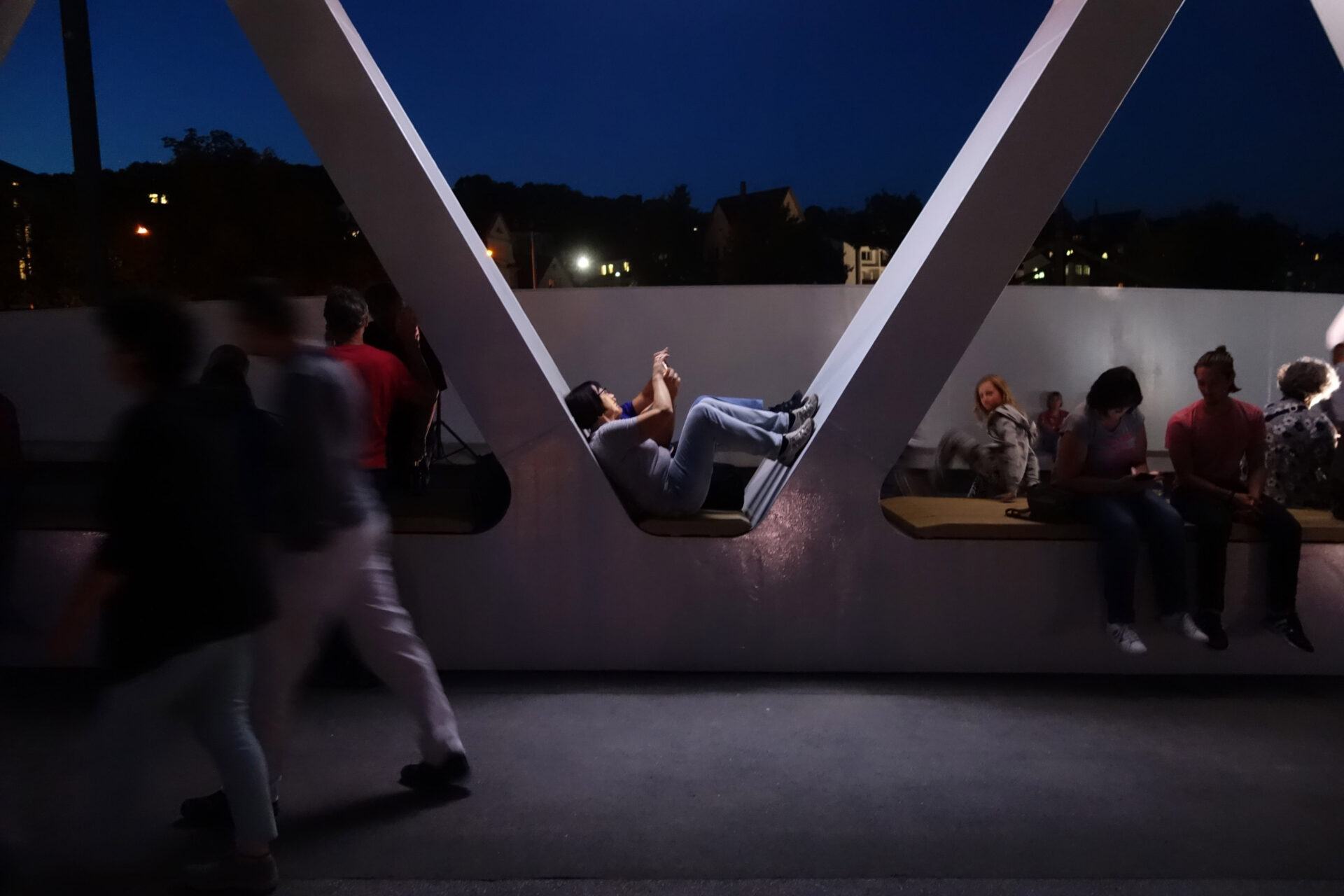 Two people sitting in archway of bridge central seating area looking at phone at night