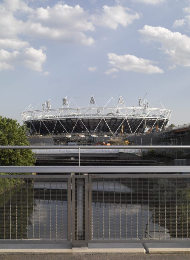 View from steel bridge parapet across river looking at the Olympic Stadium