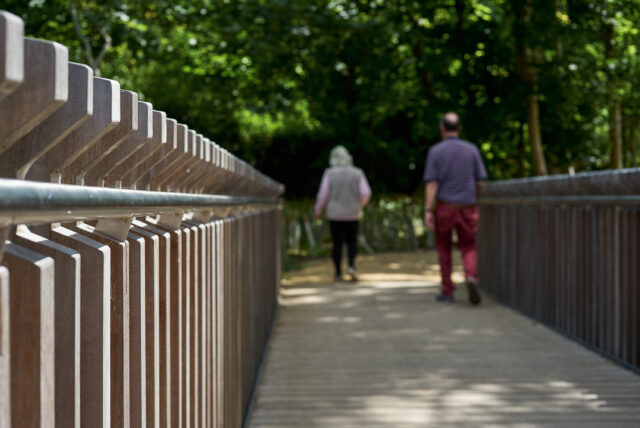 Close view of the handrail and parapet of the footbridge with people walking off the bridge in the distance