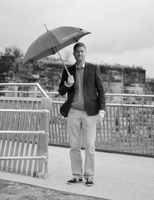 Sam White in a dark jacket holding an umbrella