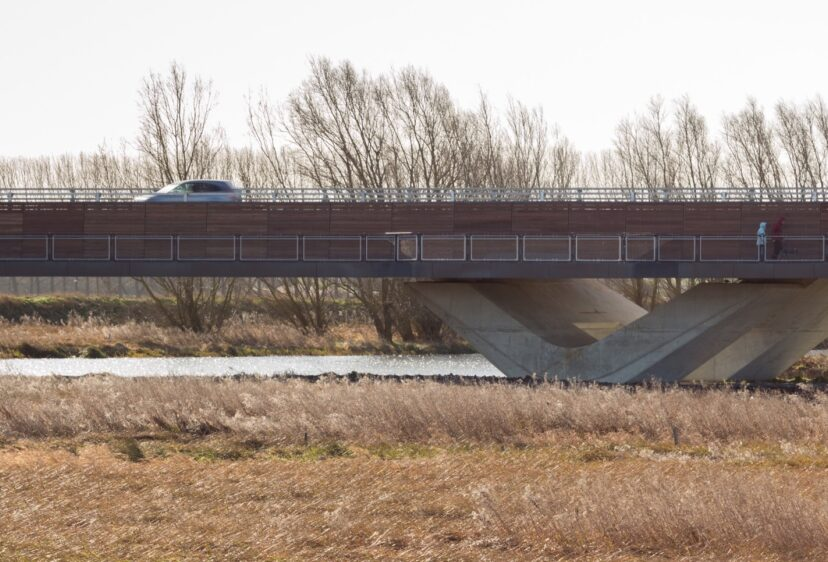 Car travelling and people walking on the Ely Bypass walkway and road