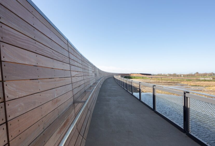 Close view of the timber walkway and parapet looking out across the river and fields in distance