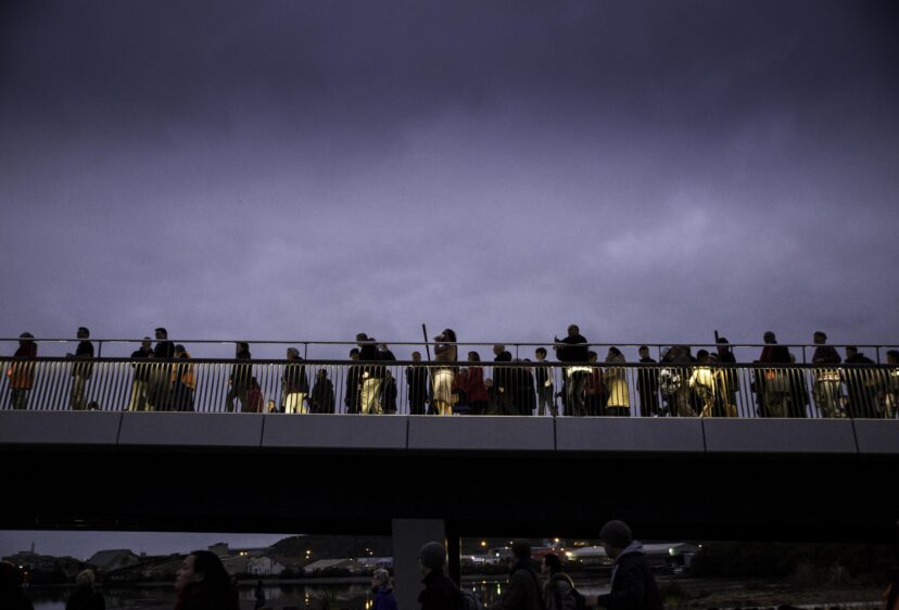 Silhouettes of people against  a cloud sky on the bridge at the opening ceremony.