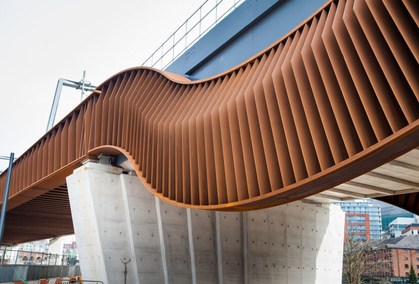 Close view of the curvaceous form of the bridge, made of weathering steel