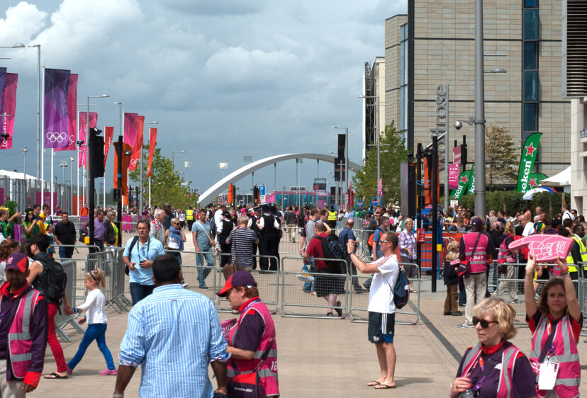 People gathering in Olympic park with Stratford Bridge 20 arch in the distance