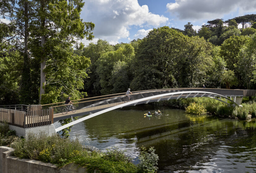 Taplow footbridge looking East with kayaks on the river and pedestrians on the bridge
