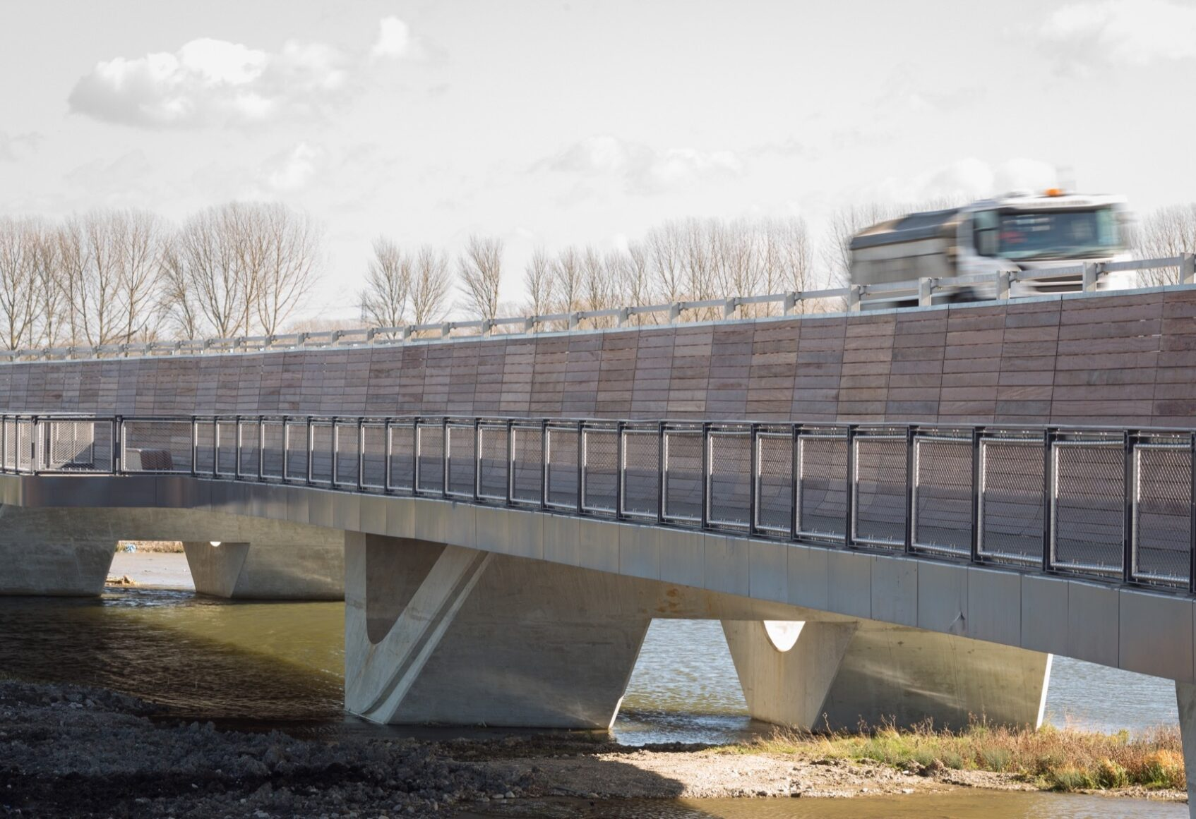 Lorry travelling at speed along road above walkway on Ely Bypass