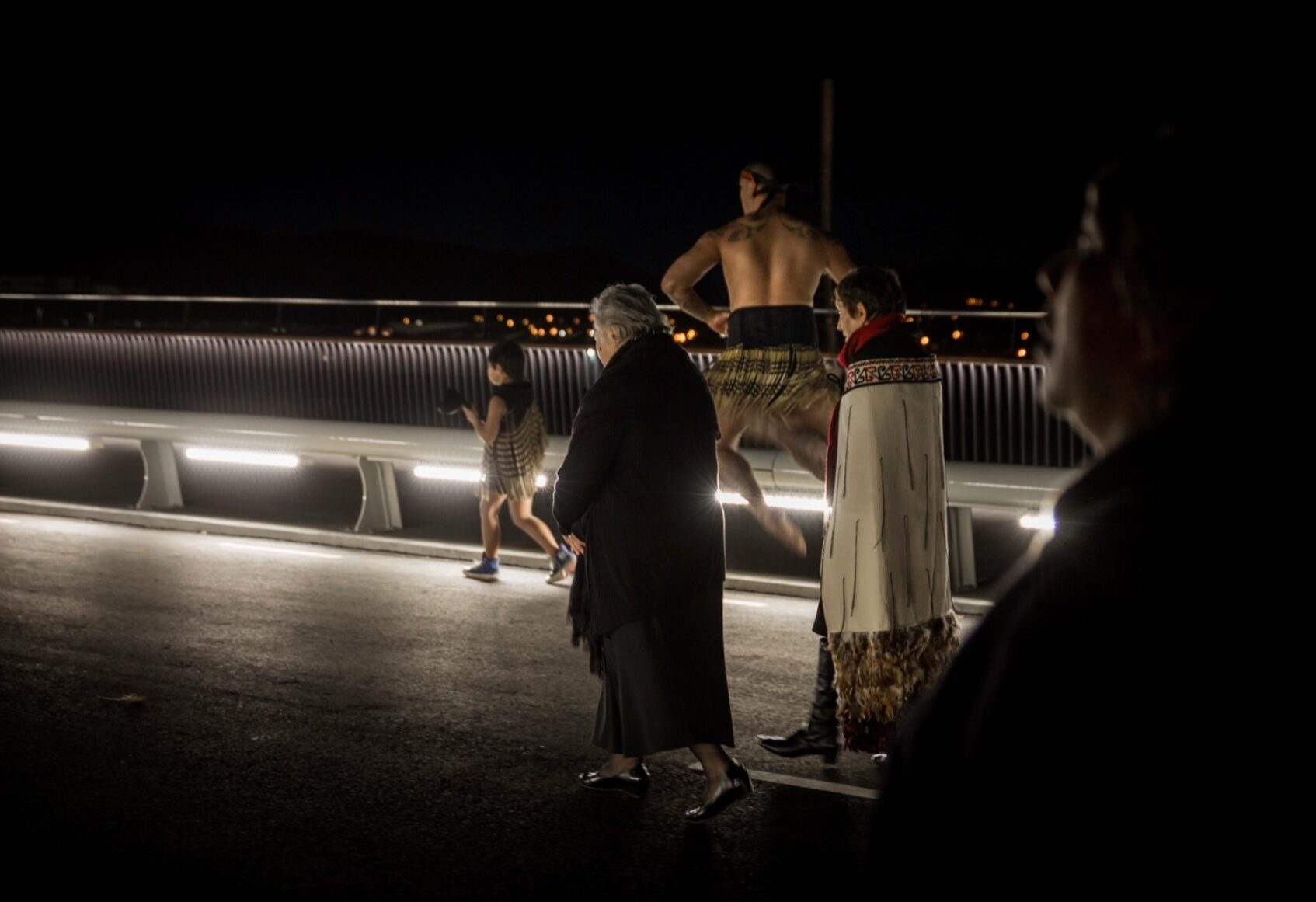 Maori people at opening ceremony walking across the deck at night with bridge lighting