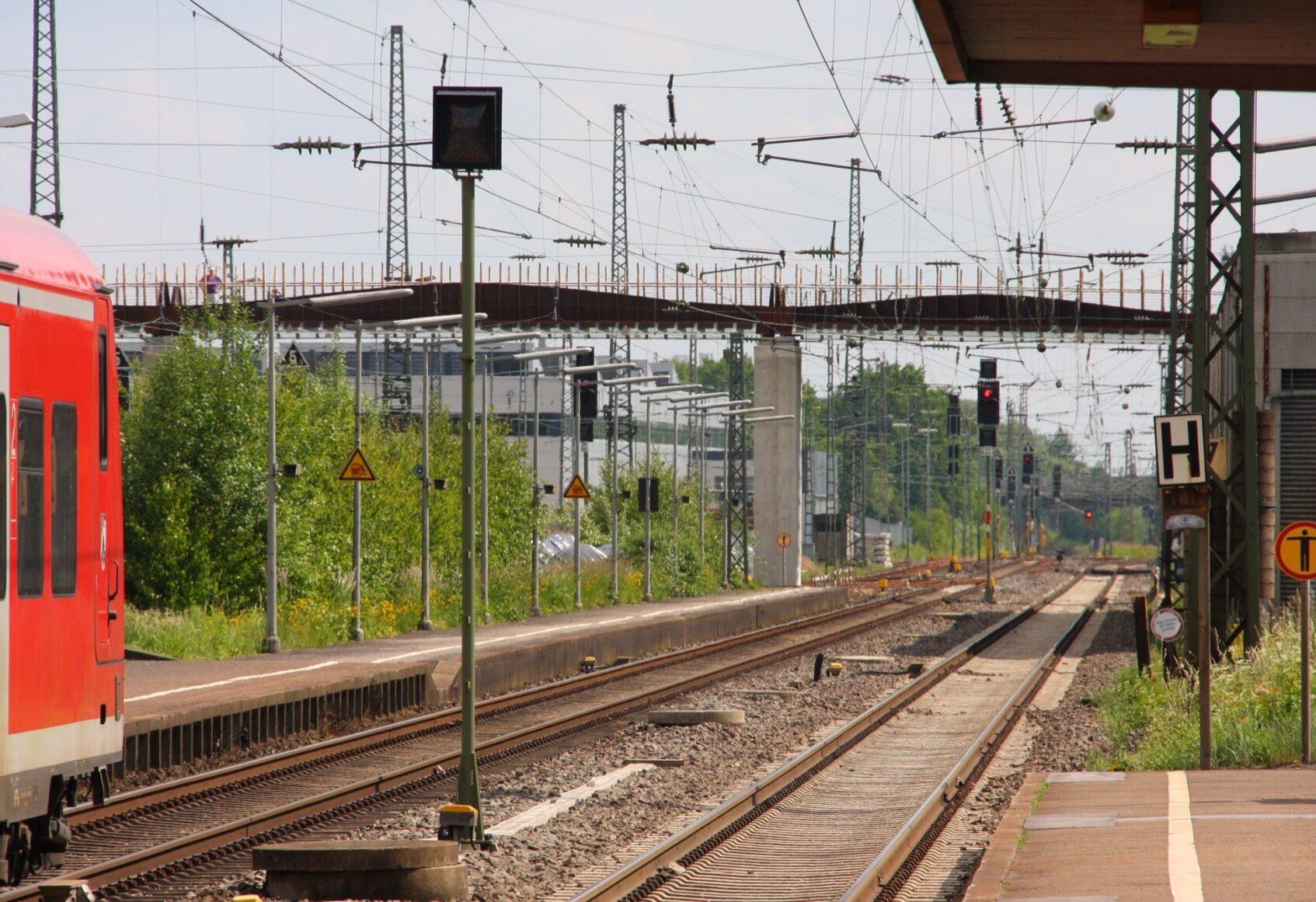 Train on left approaching underneath of bridge in distance